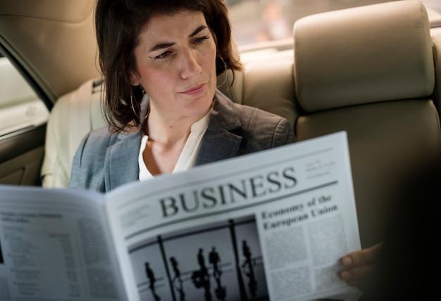 Empresaria leyendo periódico coche dentro
