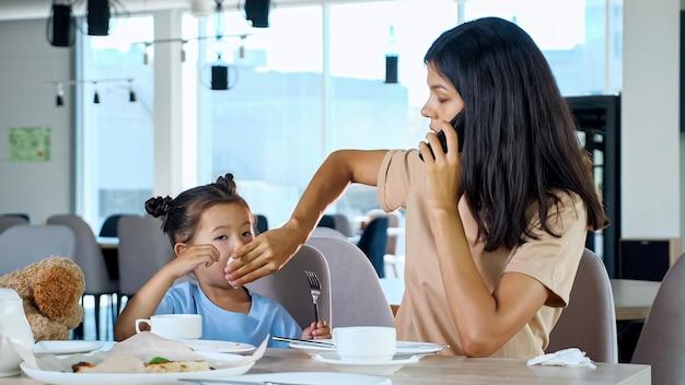 La empresaria limpia la boca del niño hablando por teléfono inteligente en el café