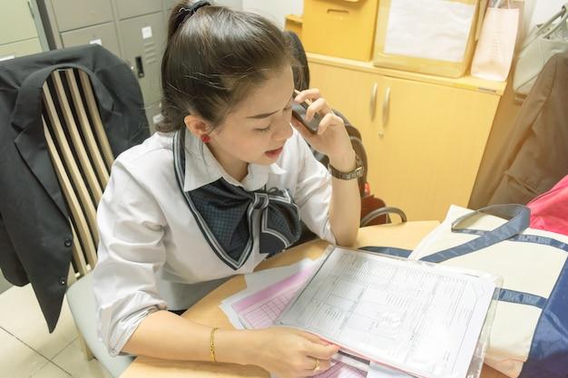 Empresaria está llamando trabajando en la oficina. escribiendo documento financiero