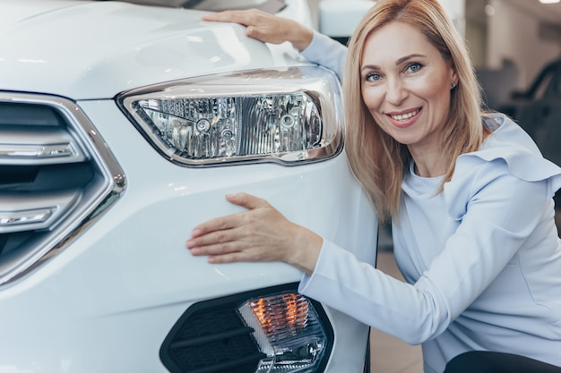 Empresaria madura abrazando a su nuevo automóvil sonriendo a la cámara.