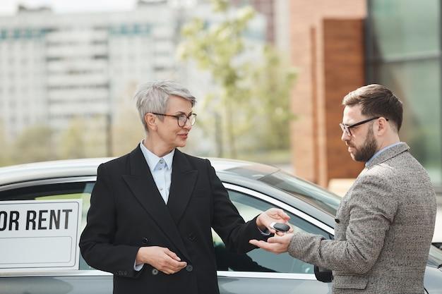 Empresaria madura dando las llaves del coche al empresario que lo alquila están de pie al aire libre