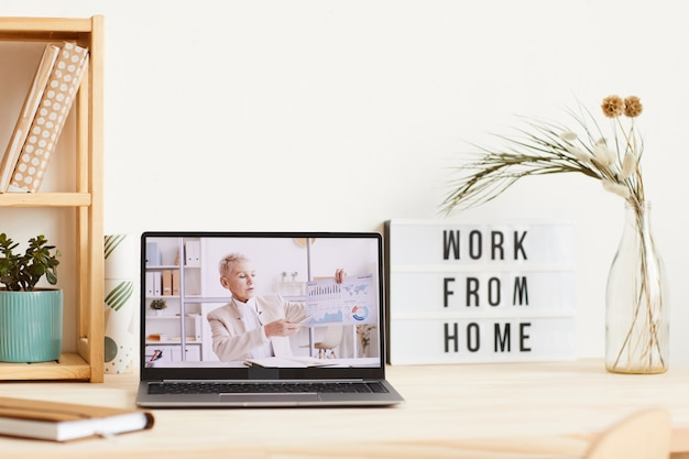 Empresaria madura con gráficos financieros y presentación de negocios en línea desde el monitor de la computadora portátil