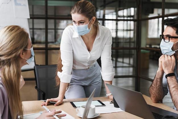 Empresaria con máscara médica sosteniendo una reunión profesional