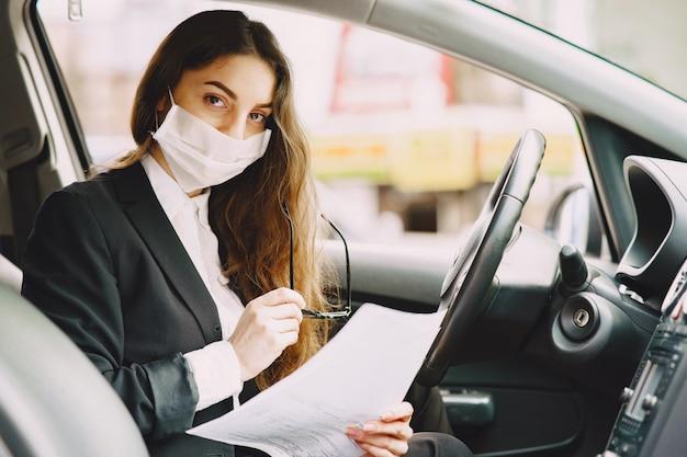 Empresaria en una máscara negra sentada dentro de un automóvil
