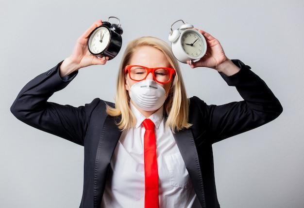 Empresaria en mascarilla y gafas rojas con despertadores