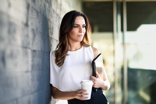 Empresaria de mediana edad que toma un descanso para tomar café en un edificio de oficinas.