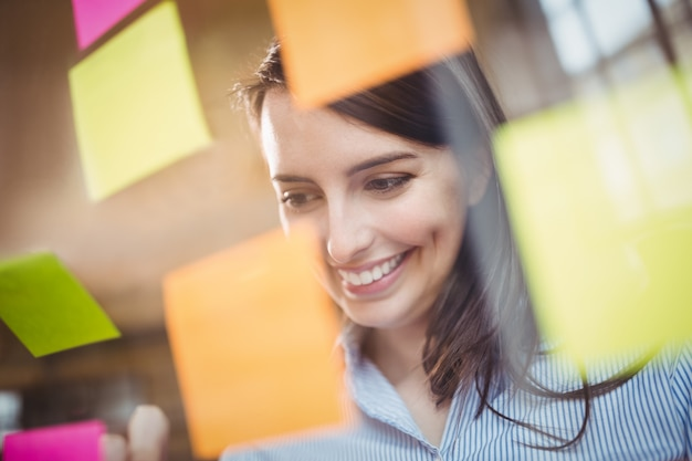 Empresaria mirando notas adhesivas pegadas al vidrio