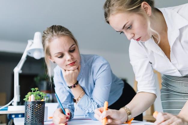 Empresaria mirando a su colega dibujando la tabla en la oficina
