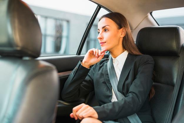Empresaria mirando a través de la ventana mientras viaja en coche