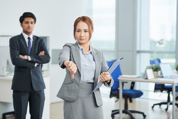 Empresaria mostrando el pulgar hacia abajo gesto, y el hombre en traje con los brazos cruzados