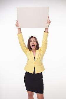 Empresaria mostrando tablero o banner con copia espacio sobre fondo blanco.
