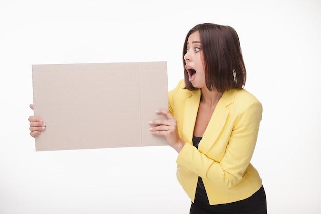 Empresaria mostrando tablero o banner con espacio de copia en la pared blanca
