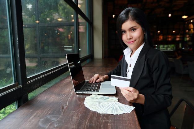 Empresaria mostrando tarjeta de crédito con computadora y billetes en el escritorio de madera