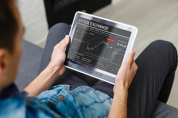 Empresaria negociando acciones con tableta y gráfico