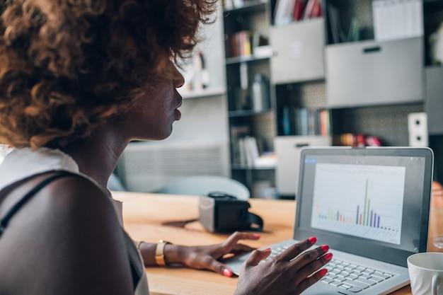 Empresaria negra joven que trabaja con el ordenador portátil en oficina moderna y que planea un proyecto