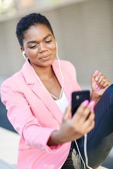 Empresaria negra sentada al aire libre hablando por videoconferencia con su teléfono inteligente.