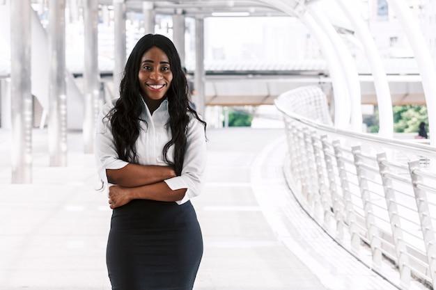 Empresaria negra sonriente con los brazos cruzados