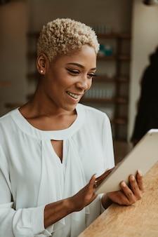Empresaria negra con una tableta digital en un café