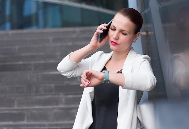 Empresaria ocupada hablando por teléfono celular y mirando su reloj inteligente.