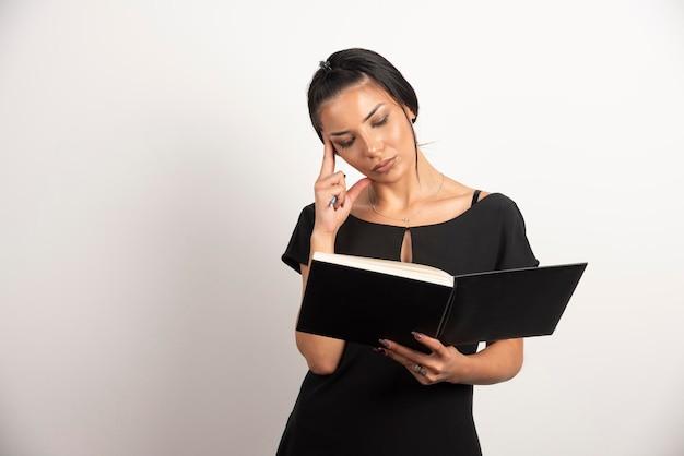 Empresaria ocupada leyendo notas en la pared blanca.