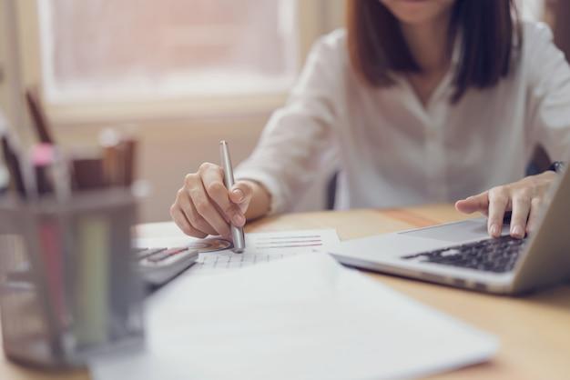 Empresaria en oficina y uso de computadora y calculadora para realizar contabilidad financiera.