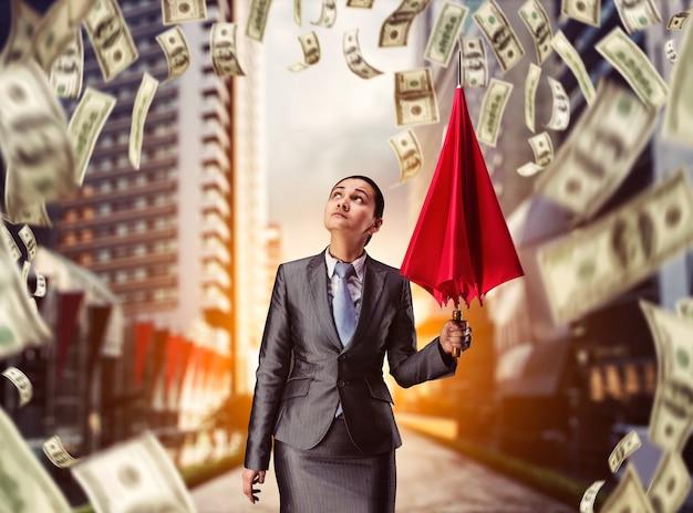 Empresaria con paraguas en lluvia de dinero