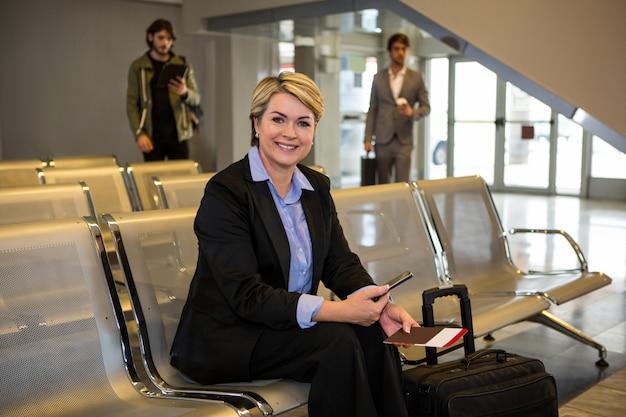 Empresaria con pasaporte, tarjeta de embarque y equipaje sentado en la sala de espera