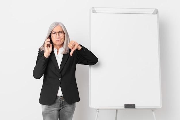 Empresaria de pelo blanco de mediana edad con un espacio de copia de tablero vacío.