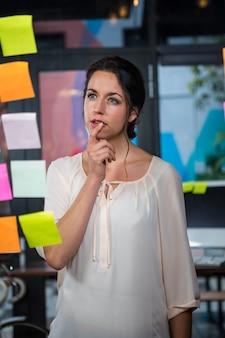 Empresaria pensativa con notas adhesivas