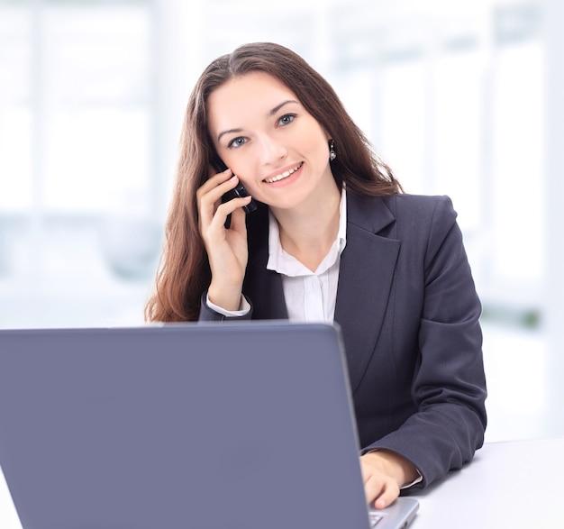 Empresaria pensativa en la oficina, la conversación por teléfono, sonriendo.