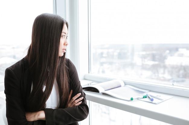 Empresaria pensativa de pie y mirando la ventana en la oficina
