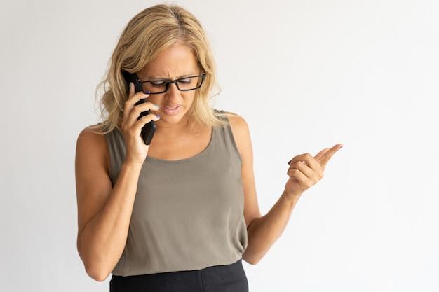 Empresaria perpleja hablando por teléfono y gesticulando con la mano