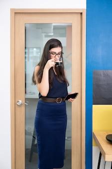 La empresaria de pie con beber café caliente en la oficina.