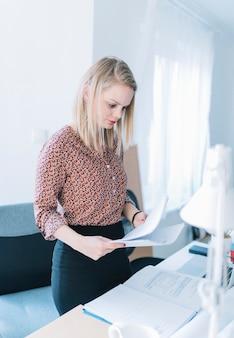 Empresaria de pie cerca del escritorio de oficina leyendo los documentos