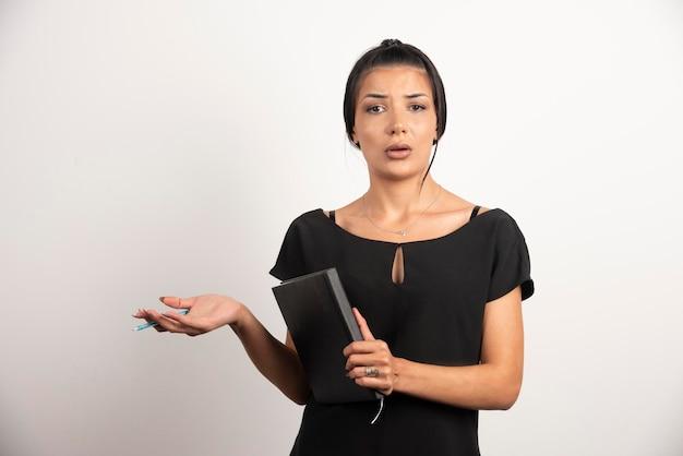 Empresaria con pie de cuaderno en la pared blanca.