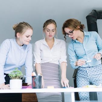 Empresaria de pie detrás del escritorio de oficina planeando el plan de negocios