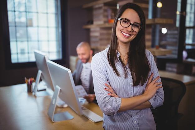 Empresaria de pie junto al escritorio mientras colega en segundo plano.