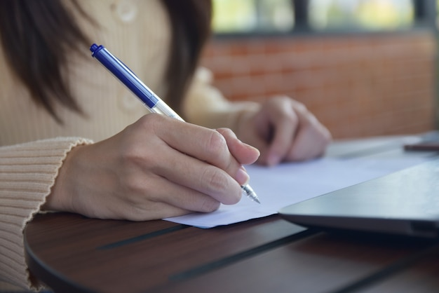 Empresaria con pluma y escribir en papel