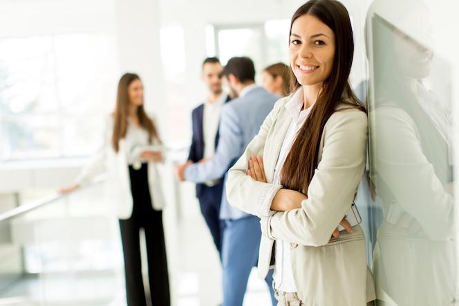 Empresaria posando mientras otros empresarios hablando en el fondo