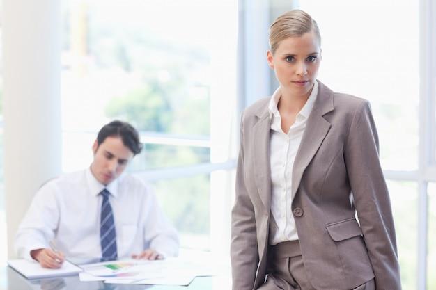 Empresaria posando mientras su colega está trabajando