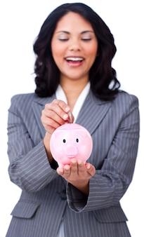 Empresaria positiva que ahorra el dinero en un piggybank