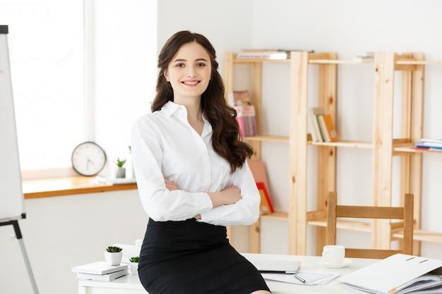 La empresaria profesional madura sonriente con los brazos cruzó sentarse en el escritorio en oficina.