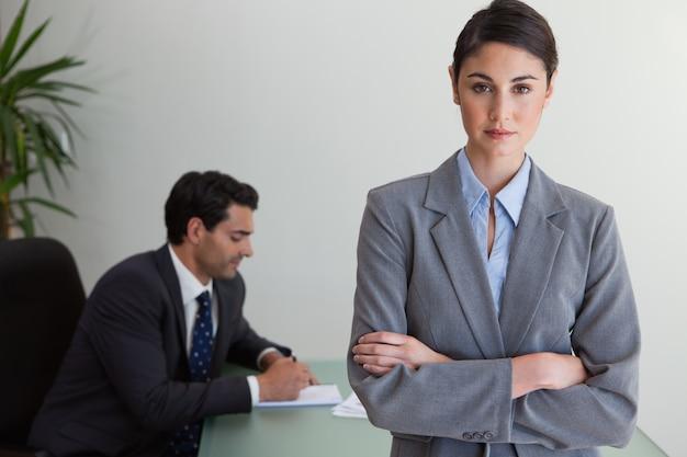 Empresaria profesional posando mientras su colega está trabajando