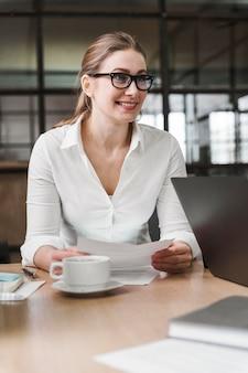 Empresaria profesional sonriente con gafas durante una reunión