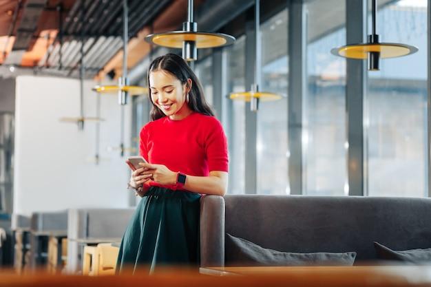 Empresaria prometedora joven empresaria exitosa prometedora de pie en su propio restaurante