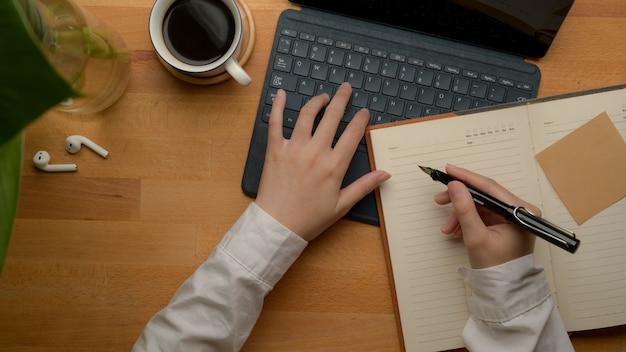 Empresaria que analiza datos comerciales en tableta digital y toma nota en el cuaderno en blanco