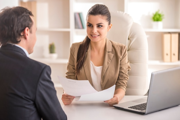 Empresaria que entrevista al candidato masculino para el trabajo en oficina.