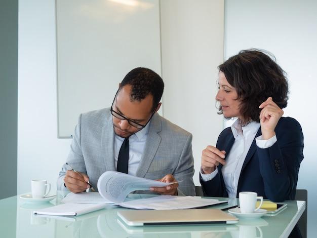 Empresaria que espera a su socio que firma el contrato