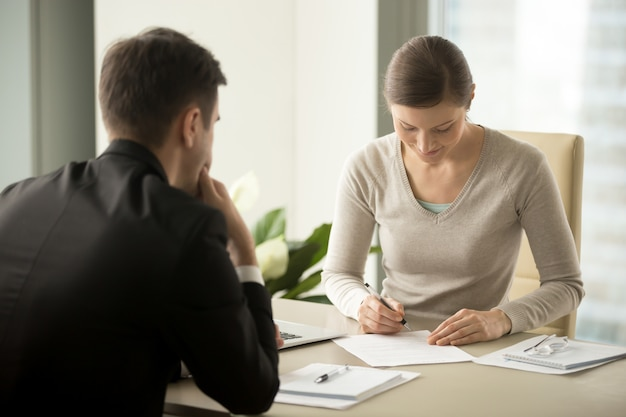 Empresaria que firma el contrato con el hombre de negocios