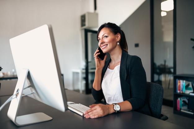 Empresaria que hace llamada mientras que se sienta en la oficina delante del ordenador.